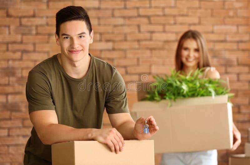 Νέο ζεύγος με το κλειδί και περιουσίες στο καινούργιο σπίτι τους στοκ φωτογραφίες