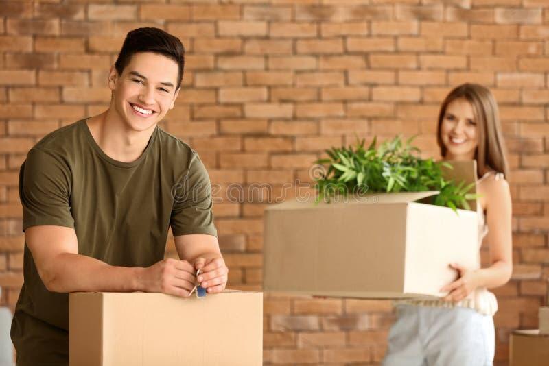 Νέο ζεύγος με το κλειδί και περιουσίες στο καινούργιο σπίτι τους στοκ εικόνα με δικαίωμα ελεύθερης χρήσης