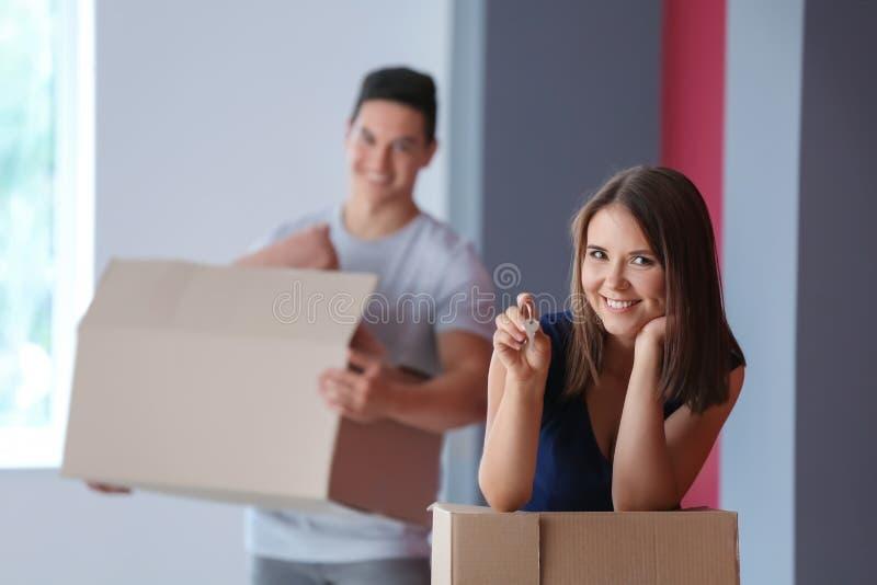 Νέο ζεύγος με το κλειδί και περιουσίες στο καινούργιο σπίτι τους στοκ εικόνες