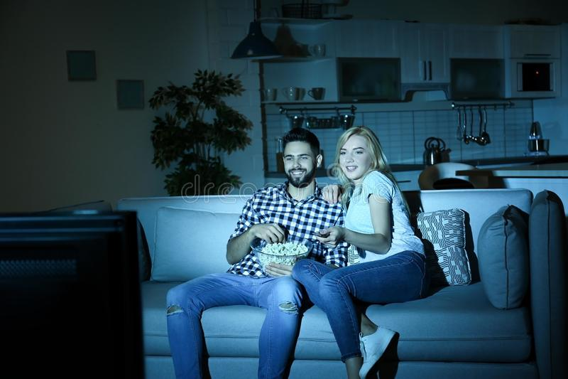 Νέο ζεύγος με το κύπελλο popcorn που προσέχει τη TV στον καναπέ στοκ φωτογραφία με δικαίωμα ελεύθερης χρήσης