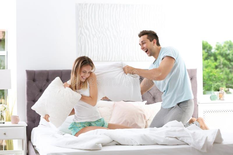 Νέο ζεύγος που έχει την πάλη μαξιλαριών στο κρεβάτι στοκ φωτογραφία με δικαίωμα ελεύθερης χρήσης