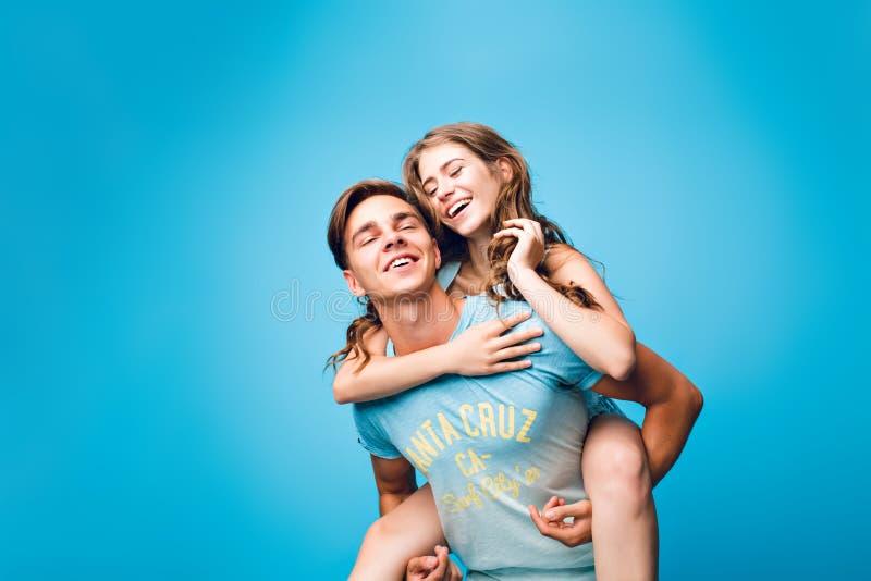 Νέο ζεύγος που έχει τη διασκέδαση στο μπλε υπόβαθρο στο στούντιο Το όμορφο κορίτσι με τη μακριά σγουρή τρίχα οδηγά στο πίσω μέρος στοκ εικόνα