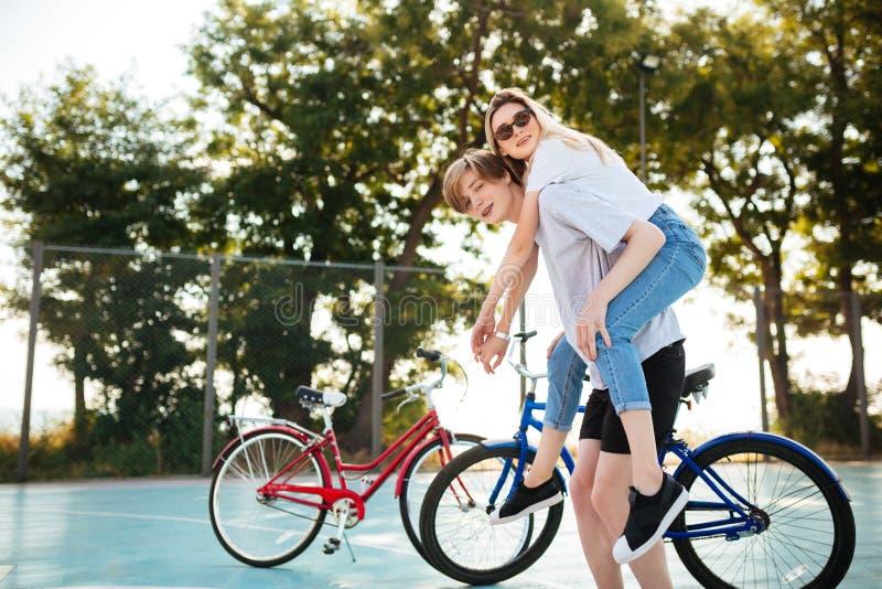 Νέο ζεύγος που έχει τη διασκέδαση στο πάρκο με το κόκκινο και μπλε ποδήλατο στο υπόβαθρο Χαμογελώντας αγόρι που φαίνεται κεκλεισμ στοκ εικόνες
