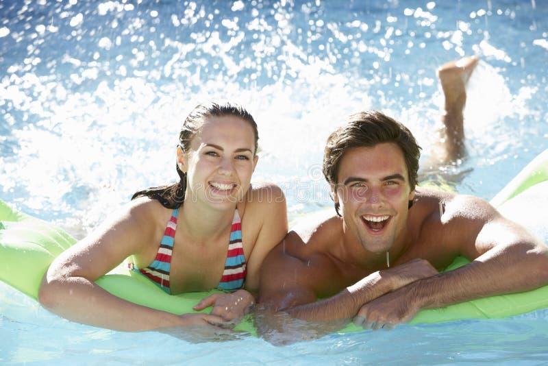 Νέο ζεύγος που έχει τη διασκέδαση με τη διογκώσιμη πισίνα Airbed από κοινού στοκ φωτογραφία