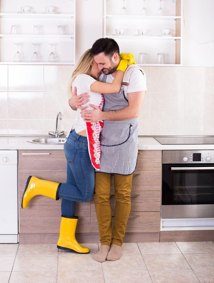 Νέο ζεύγος που αγκαλιάζει μετά από τα οικιακά στοκ φωτογραφία