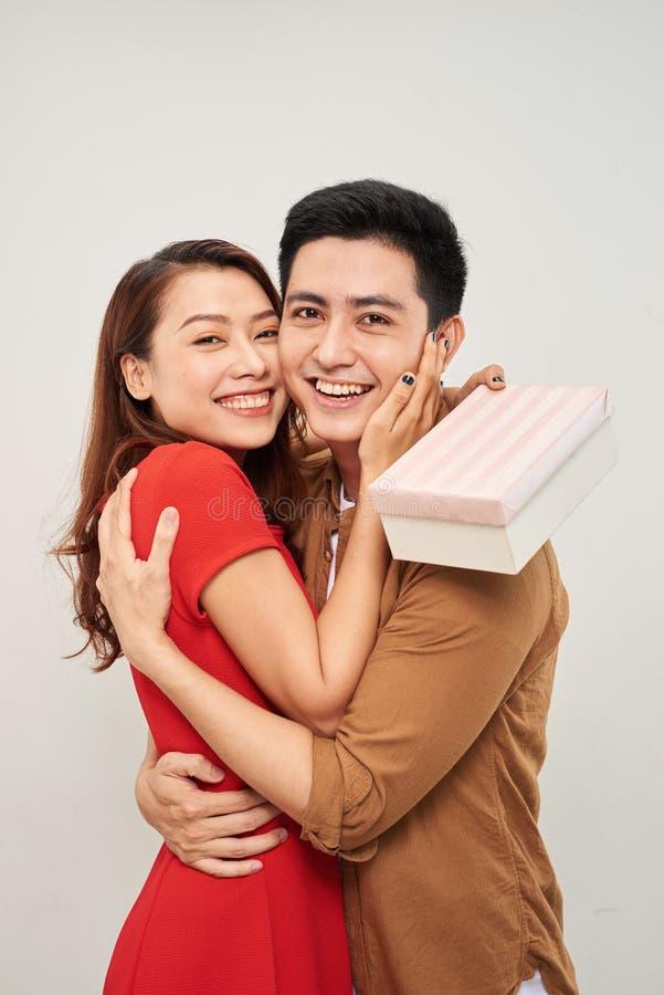 Νέο ζεύγος που αγκαλιάζει με το τυλιγμένο παρόν γυναίκα που αγκαλιάζει τον άνδρα και που κρατά παρών με την κορδέλλα στοκ εικόνες με δικαίωμα ελεύθερης χρήσης