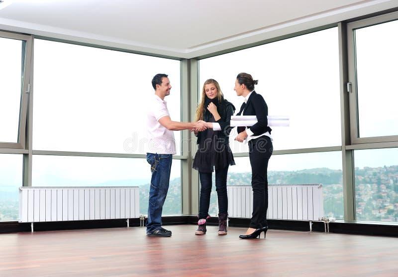 Νέο ζεύγος που αγοράζει το νέο σπίτι με το κτηματομεσίτη στοκ φωτογραφίες
