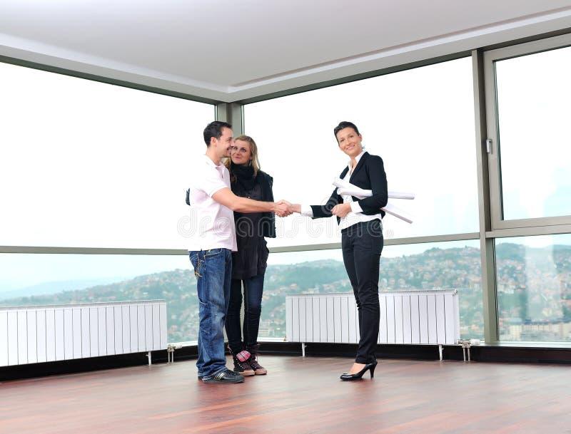 Νέο ζεύγος που αγοράζει το νέο σπίτι με το κτηματομεσίτη στοκ εικόνες με δικαίωμα ελεύθερης χρήσης