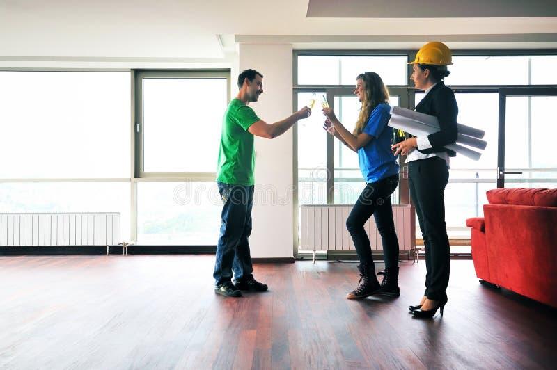 Νέο ζεύγος που αγοράζει το νέο σπίτι με το κτηματομεσίτη στοκ εικόνες