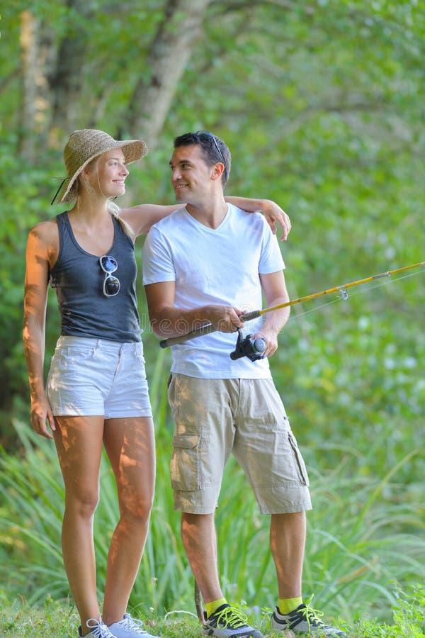 Νέο ζεύγος που αλιεύει στην ακτή ποταμών στη χλόη στοκ εικόνες με δικαίωμα ελεύθερης χρήσης