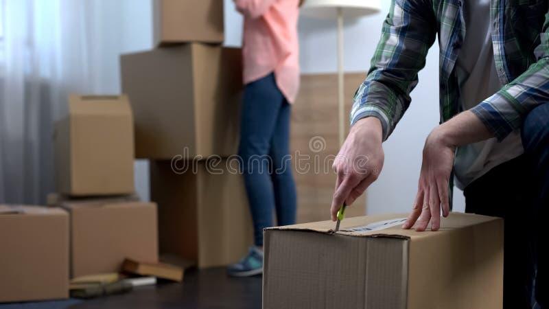Νέο ζεύγος που ανοίγει τα πράγματά τους στο νέο διαμέρισμα, απόφαση να ζήσει από κοινού στοκ φωτογραφία με δικαίωμα ελεύθερης χρήσης