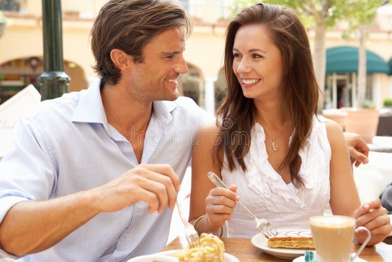 Νέο ζεύγος που απολαμβάνει τον καφέ και το κέικ στοκ φωτογραφία