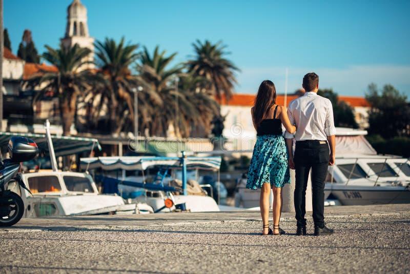 Νέο ζεύγος που απολαμβάνει το χρόνο διακοπών Φίλος και φίλη που έχουν έναν ρομαντικό περίπατο κατά μήκος της ακτής σε μια πόλη πα στοκ φωτογραφία με δικαίωμα ελεύθερης χρήσης