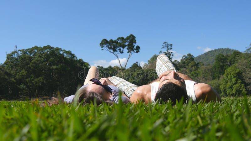 Νέο ζεύγος που βρίσκεται στην πράσινη χλόη στο πάρκο και τη χαλάρωση Συνεδρίαση ανδρών και γυναικών στο λιβάδι στη φύση και το φί στοκ φωτογραφία με δικαίωμα ελεύθερης χρήσης