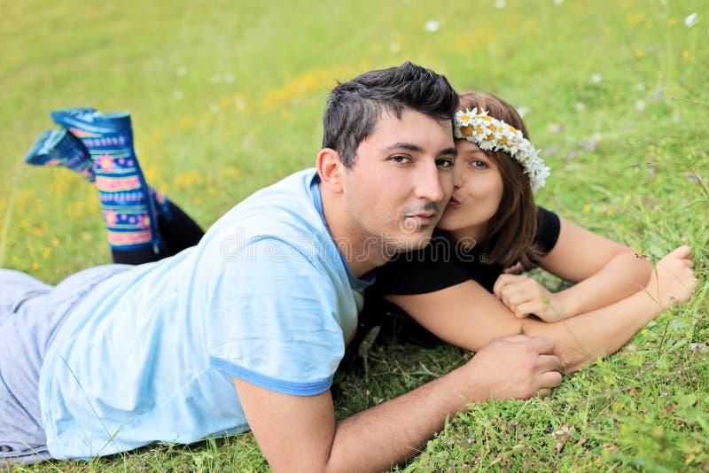 Νέο ζεύγος που βρίσκεται στη χλόη σε ένα λιβάδι στοκ φωτογραφία με δικαίωμα ελεύθερης χρήσης