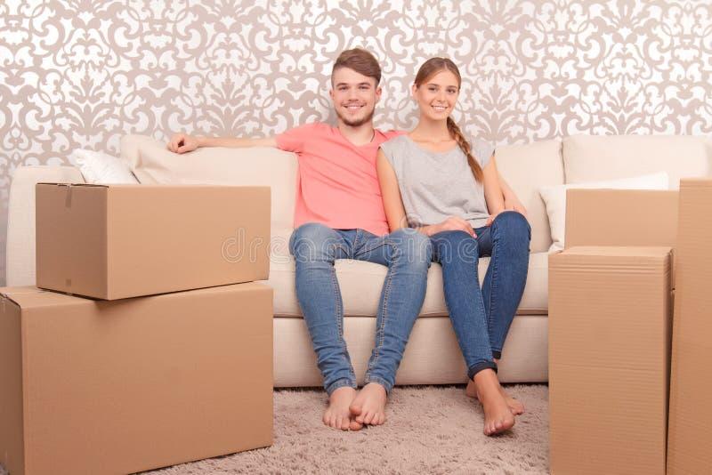 Νέο ζεύγος που εγκαθιστά στον καναπέ στοκ φωτογραφία με δικαίωμα ελεύθερης χρήσης