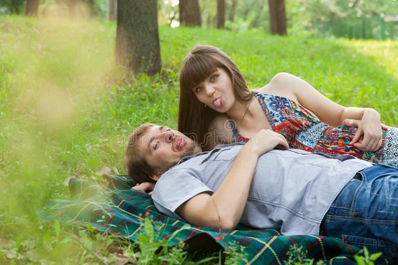 Νέο ζεύγος που εμφανίζει γλώσσες τους στο φωτογράφο στοκ φωτογραφία