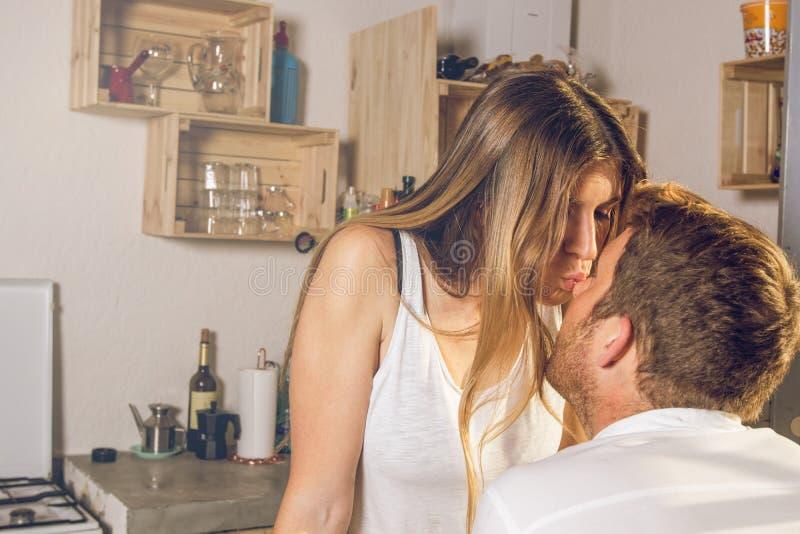 Νέο ζεύγος που εξετάζει το ένα το άλλο και που φιλά στην κουζίνα ευτυχή στοκ εικόνες με δικαίωμα ελεύθερης χρήσης
