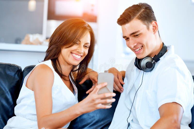 Νέο ζεύγος που εξετάζει το κινητό τηλέφωνο καθμένος στο σπίτι στοκ φωτογραφία