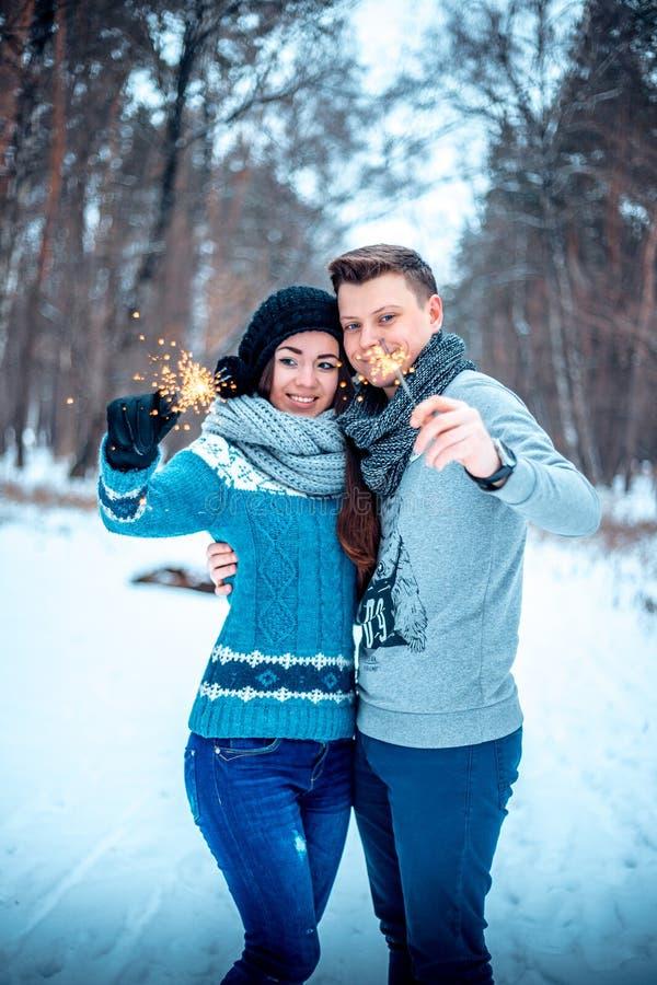 Νέο ζεύγος που εξετάζει το χειμερινό δάσος sparklers στοκ φωτογραφία