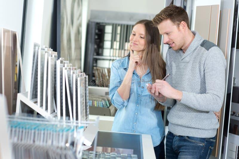 Νέο ζεύγος που επιλέγει από swatch κεραμιδιών γυαλιού στοκ φωτογραφία με δικαίωμα ελεύθερης χρήσης