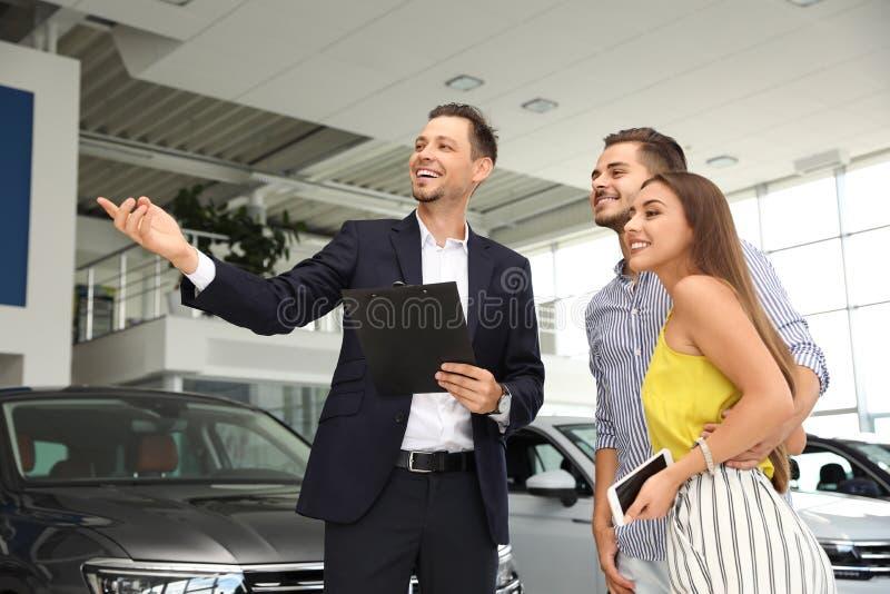 Νέο ζεύγος που επιλέγει το νέο αυτοκίνητο με τον πωλητή στοκ φωτογραφία με δικαίωμα ελεύθερης χρήσης