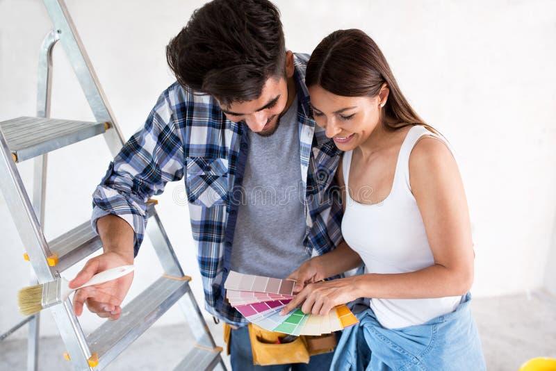 Νέο ζεύγος που επιλέγει τα χρώματα για τη ζωγραφική του σπιτιού τους στοκ εικόνες