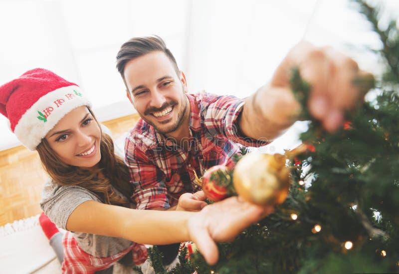 Νέο ζεύγος που διακοσμεί ένα χριστουγεννιάτικο δέντρο στοκ φωτογραφίες