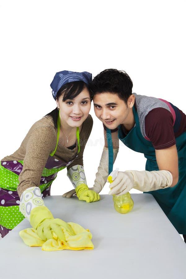 Νέο ζεύγος που καθαρίζει έναν πίνακα στοκ φωτογραφία
