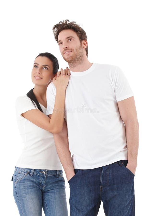 Νέο ζεύγος που κοιτάζει στην απόσταση που χαμογελά προς τα πάνω στοκ φωτογραφία με δικαίωμα ελεύθερης χρήσης