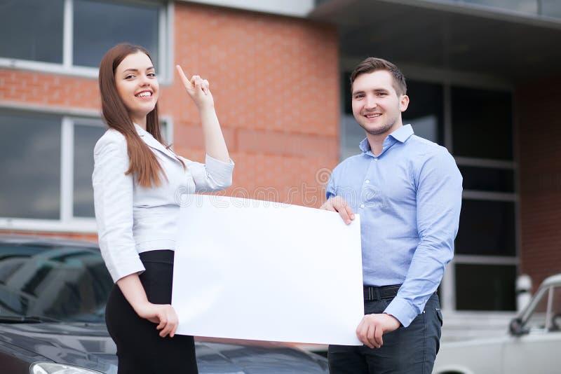 Νέο ζεύγος που κρατά ένα άσπρο φύλλο σε ένα υπόβαθρο του αυτοκινήτου στοκ φωτογραφίες με δικαίωμα ελεύθερης χρήσης
