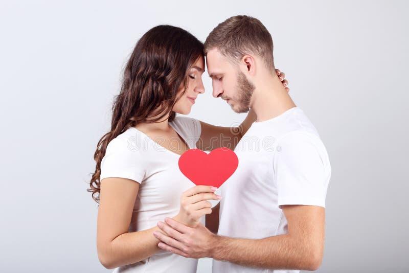 Νέο ζεύγος που κρατά την κόκκινη καρδιά εγγράφου στοκ φωτογραφία με δικαίωμα ελεύθερης χρήσης