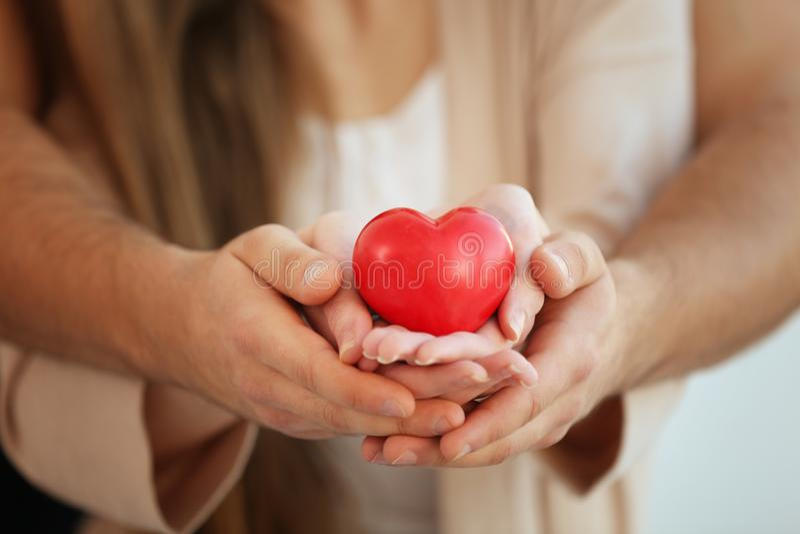Νέο ζεύγος που κρατά τη μικρή κόκκινη καρδιά, στοκ φωτογραφία με δικαίωμα ελεύθερης χρήσης