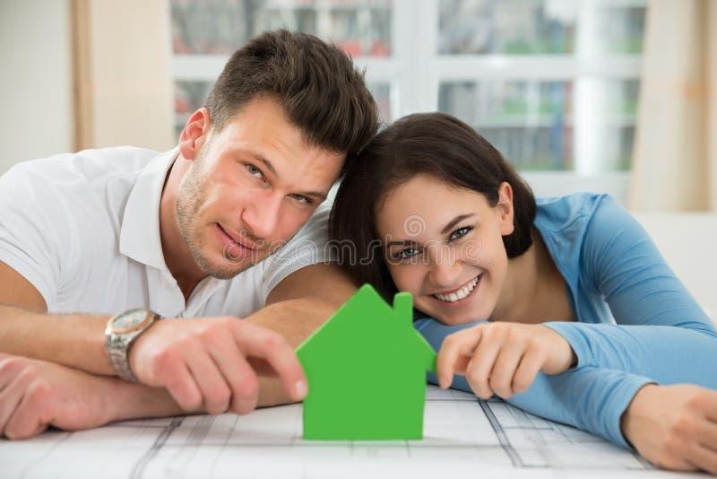 Νέο ζεύγος που κρατά το πράσινο πρότυπο σπιτιών στοκ φωτογραφία με δικαίωμα ελεύθερης χρήσης