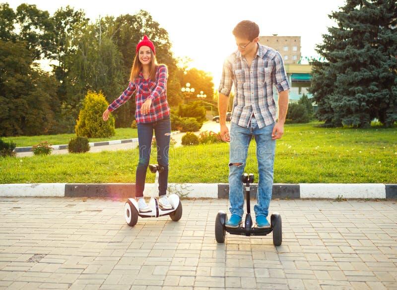 Νέο ζεύγος που οδηγά hoverboard - ηλεκτρικό μηχανικό δίκυκλο, προσωπική ΕΚ στοκ φωτογραφία