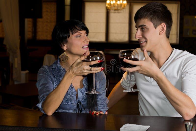 Νέο ζεύγος που πίνει το κόκκινο κρασί σε έναν μετρητή φραγμών στοκ φωτογραφία με δικαίωμα ελεύθερης χρήσης