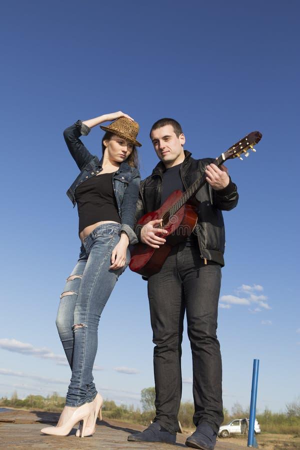 Νέο ζεύγος που παίζει την ακουστική κιθάρα στοκ φωτογραφία