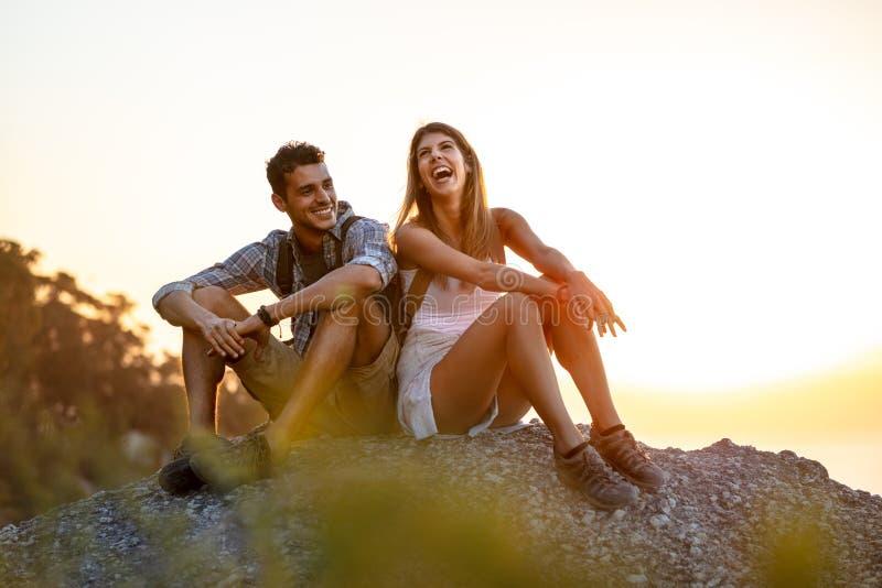 Νέο ζεύγος που παίρνει ένα σπάσιμο σε ένα πεζοπορώ Ευτυχής συνεδρίαση νεαρών άνδρων και γυναικών στην κορυφή βουνών και γέλιο στοκ φωτογραφία με δικαίωμα ελεύθερης χρήσης
