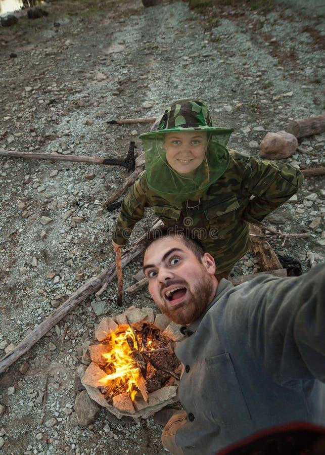 Νέο ζεύγος που παίρνει τις φωτογραφίες κοντά στη φωτιά από κοινού Πεζοπορία, ελεύθερος χρόνος, διακινούμενη έννοια στοκ εικόνα με δικαίωμα ελεύθερης χρήσης