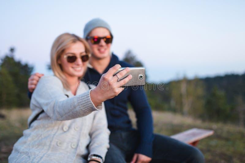 Νέο ζεύγος που παίρνει selfie στο ηλιοβασίλεμα βουνών στοκ φωτογραφίες