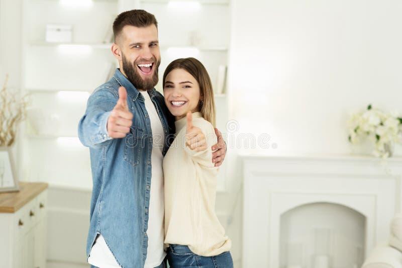 Νέο ζεύγος που παρουσιάζει αντίχειρες στο καινούργιο σπίτι στοκ φωτογραφίες