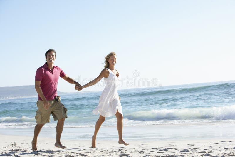 Νέο ζεύγος που περπατά κατά μήκος της αμμώδους παραλίας στις διακοπές στοκ φωτογραφία με δικαίωμα ελεύθερης χρήσης