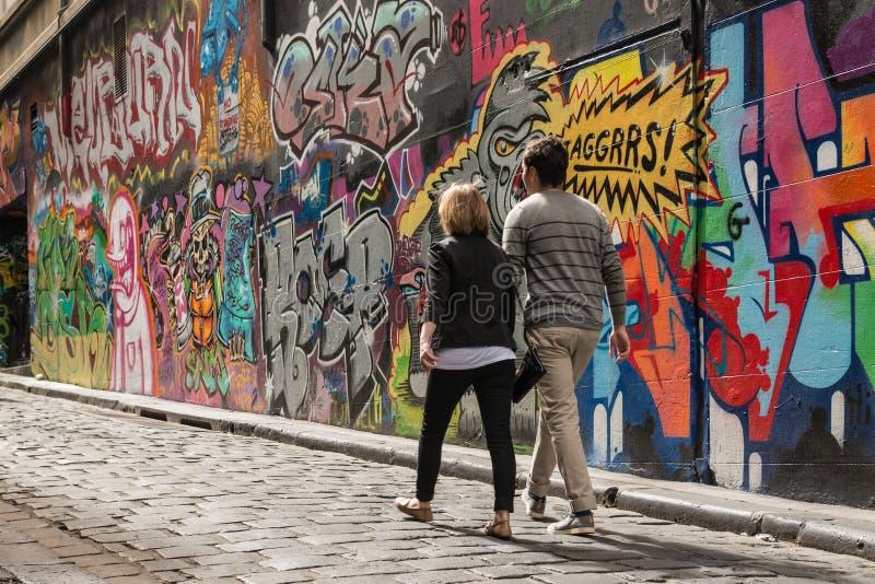 Νέο ζεύγος που περπατά μετά από τον τοίχο γκράφιτι στη Μελβούρνη στοκ εικόνες