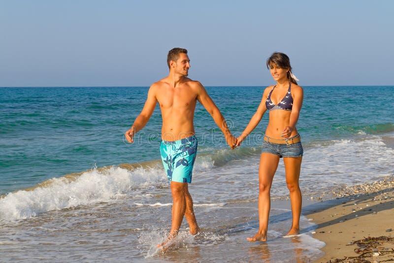 Νέο ζεύγος που περπατά στην παραλία στοκ φωτογραφίες