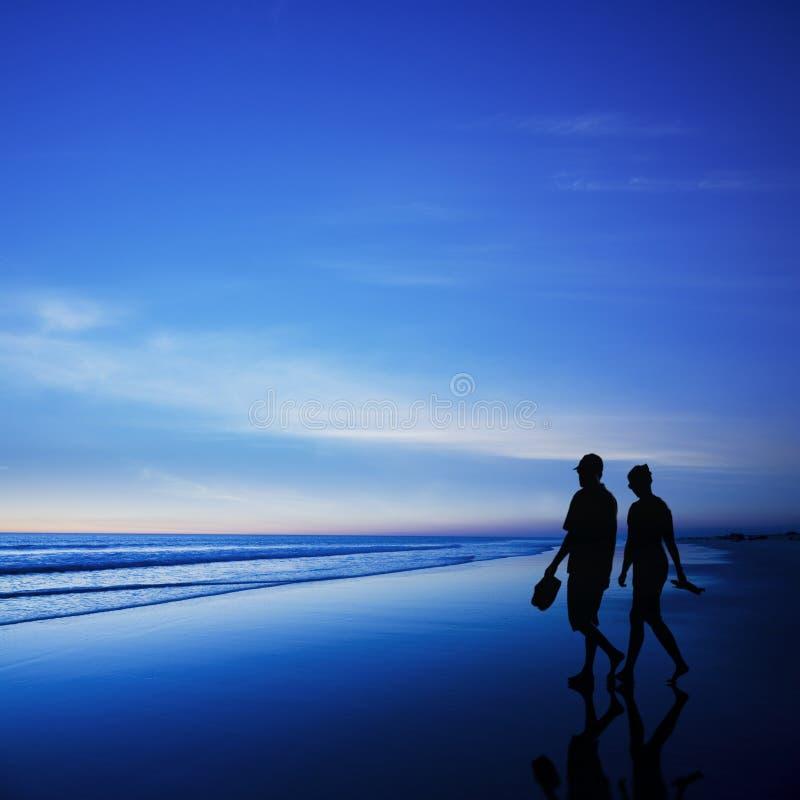 Νέο ζεύγος που περπατά στη ρομαντική παραλία στο λυκόφως στοκ φωτογραφίες με δικαίωμα ελεύθερης χρήσης