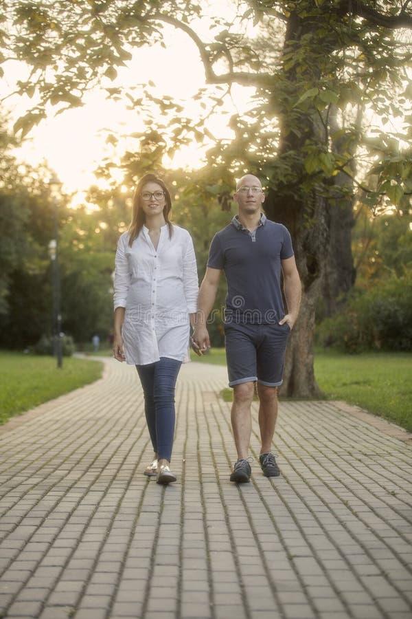 νέο ζεύγος που περπατά στο ίχνος πάρκων μπροστά ευθύς στοκ φωτογραφία με δικαίωμα ελεύθερης χρήσης