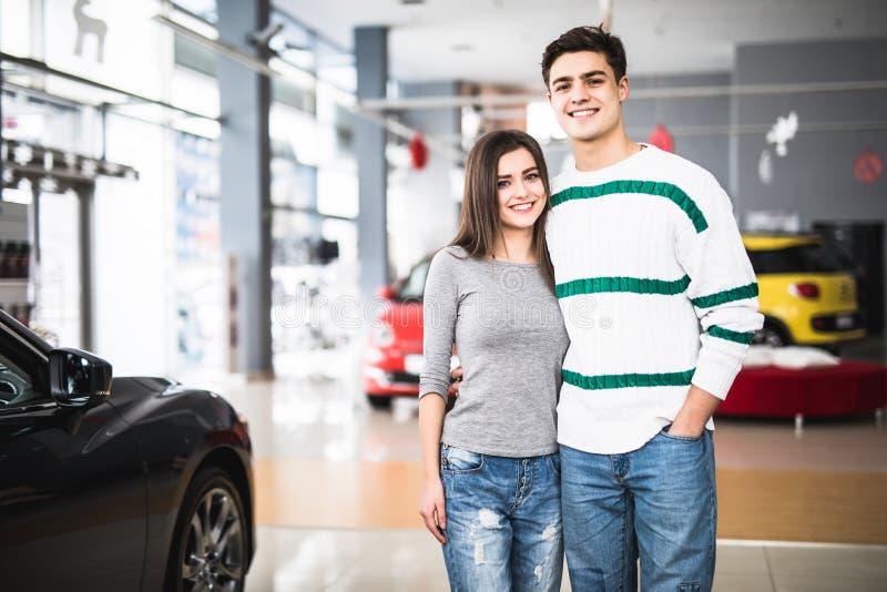 Νέο ζεύγος που στέκεται μπροστά από ένα αυτοκίνητο στο νέο αυτοκίνητο στοκ εικόνα