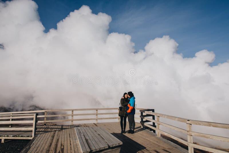 νέο ζεύγος που στέκονται μαζί και ατμός από τα γεωθερμικά καυτά ελατήρια πίσω από τα reykjanes Gunnuhver καυτό στοκ φωτογραφίες