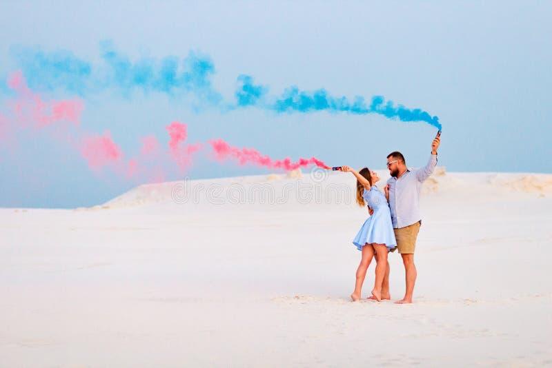 Νέο ζεύγος που στέκονται σε μια άμμο και που κρατούν τη βόμβα καπνού και που εξετάζουν το ένα το άλλο, ρομαντικό ζεύγος με το μπλ στοκ φωτογραφία με δικαίωμα ελεύθερης χρήσης
