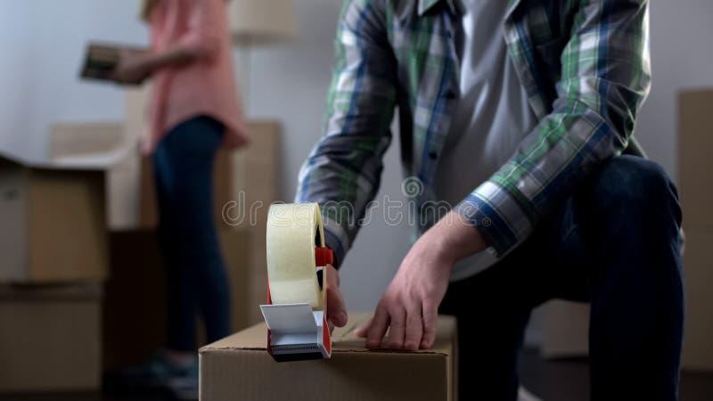 Νέο ζεύγος που συσκευάζει τα πράγματά τους στα κιβώτια, που κινούνται από τον κοιτώνα για να είναι κύριος του σπιτιού στοκ εικόνες με δικαίωμα ελεύθερης χρήσης